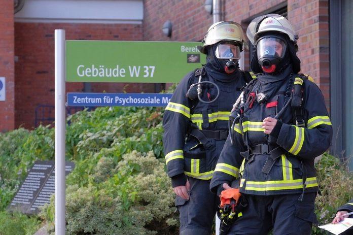 Zwei Feuerwehrleute stehen vor dem UKE in Hamburg.
