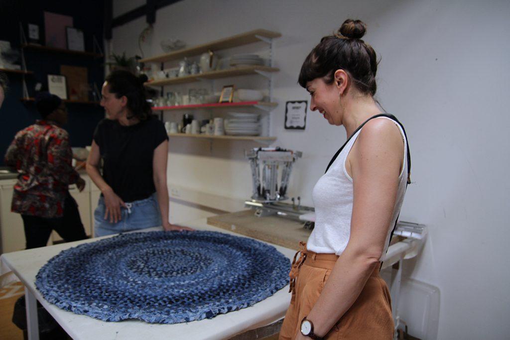 Gründerin Conny steht lachend vor einem dunkelblauen runden Teppich