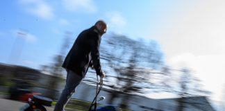 Mann fährt auf einem E-Scooter.