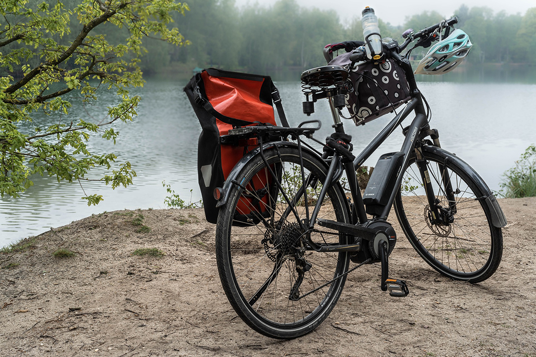 Ein E-Bike steht an einem See.