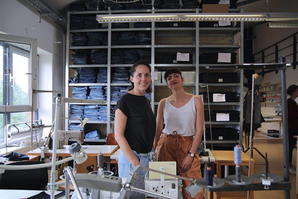Gründerinnen Lotte (links) und Conny (rechts) vor dem großen Jeansregal in der Werkstatt