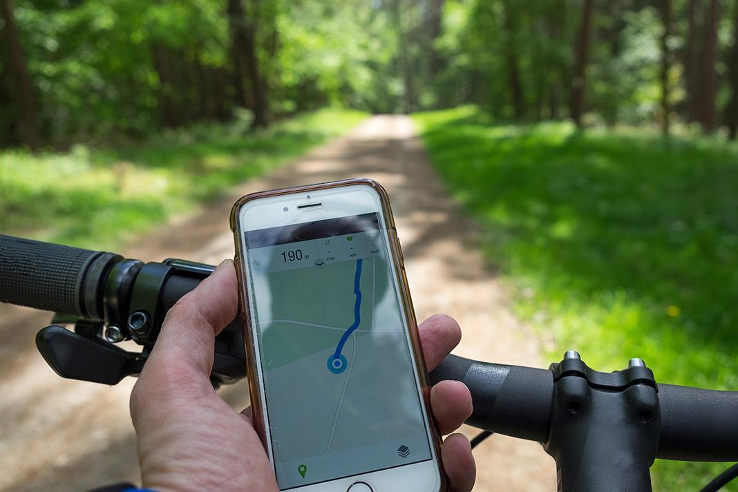 Eine Hand hält eine Handy in der Hand, während der Fahrt auf einem Fahrrad.