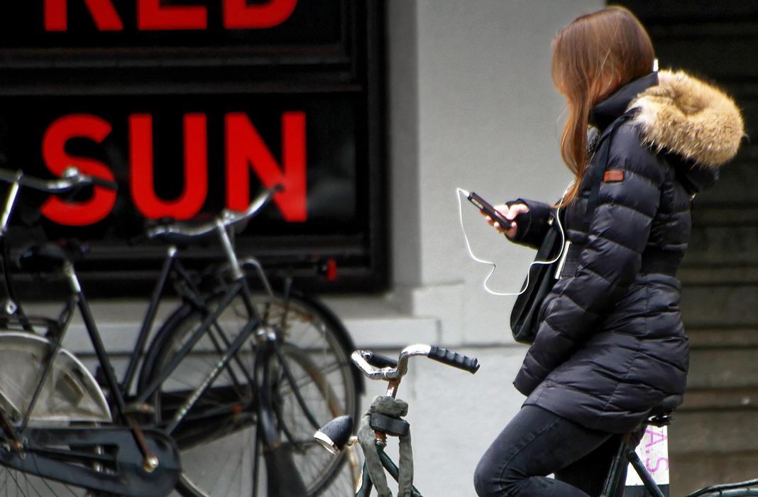 Eine Frau hält ihr Smartphone in der Hand und sitzt auf ihrem Fahrrad.