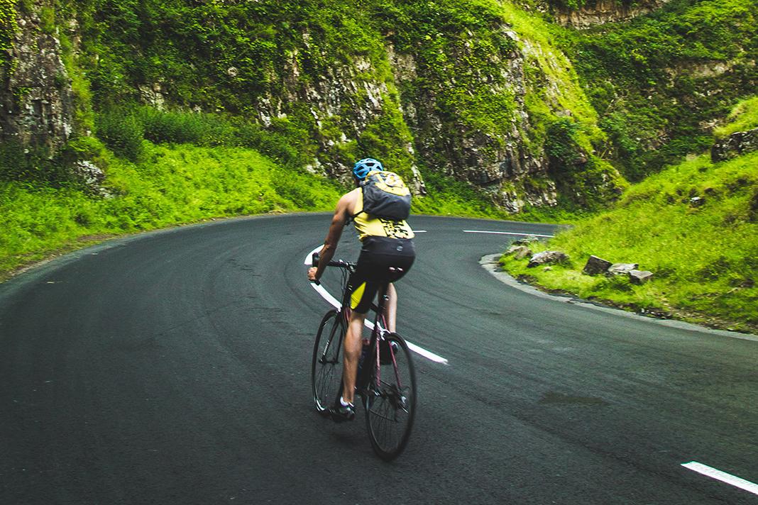 Ein Radfahrer fährt auf der linken Straßenseite eine Bergstraße runter.