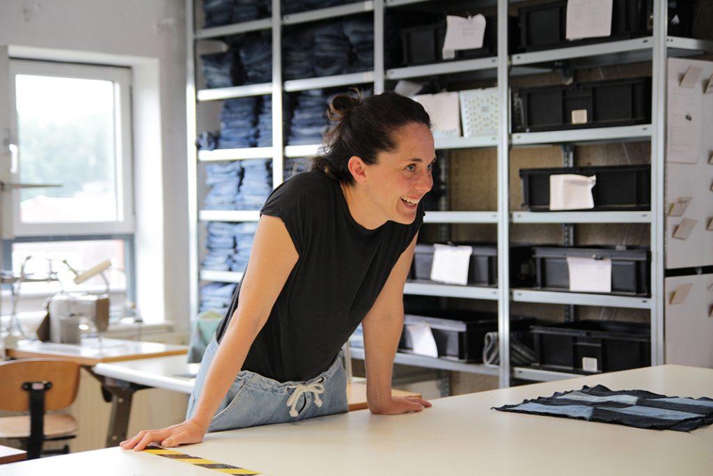 Gründerin Lotte lehnt sich lachend über den großen Arbeitstisch in der Werkstatt