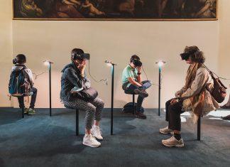 Menschen sitzen auf Stühlen und tragen VR-Brillen.