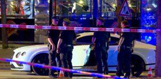 Polizisten stehen neben einem Auto eines Hells-Angels-Boss auf dem Millerntorplatz an der Reeperbahn.