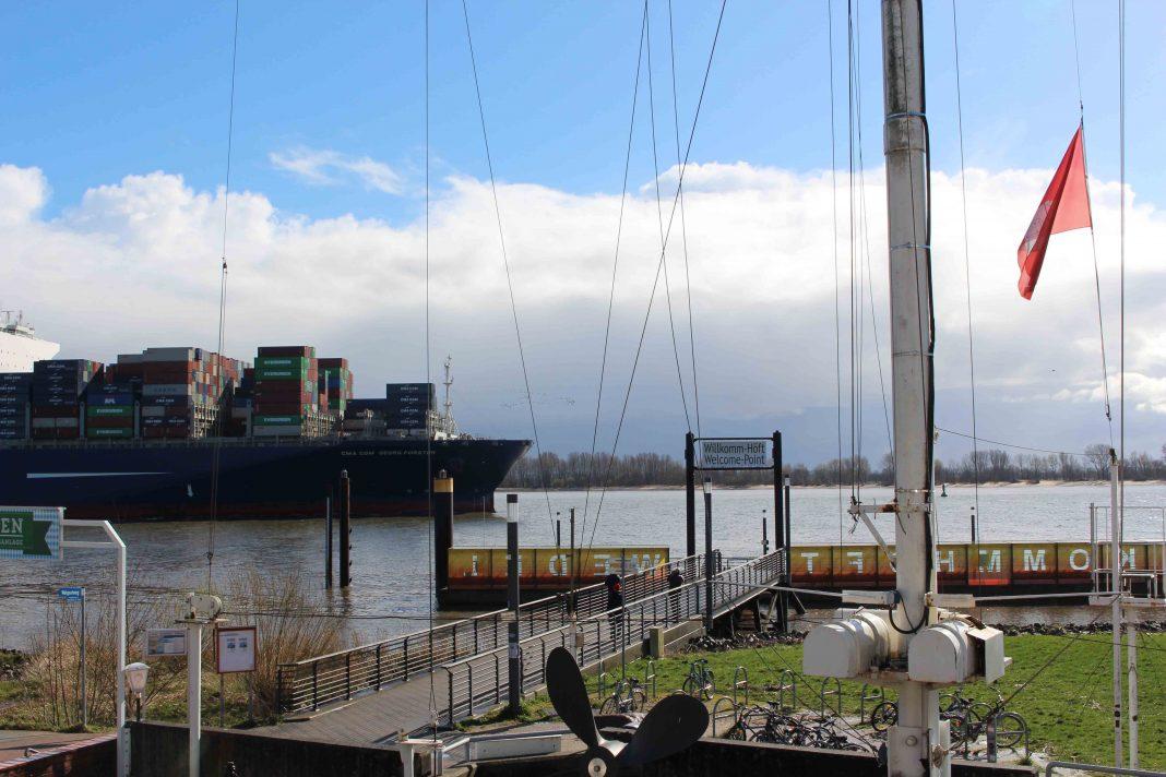 Blauer Containerfrachter fährt die Elbe entlang, im Vordergrund Biergarten der Schiffsbegrüßungsanlage Willkomm Höft.