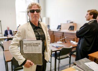 70-Jähriger mutmaßlicher Serienbankräuber steht im Gericht und hält einen Zeitungsartikel.