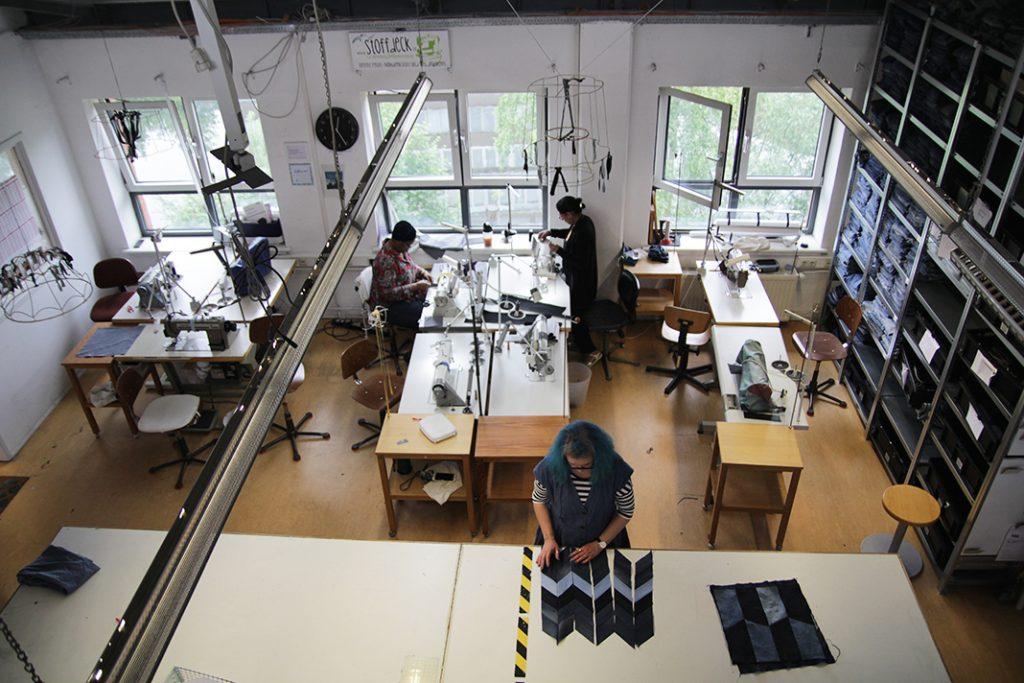 Werkstatt mit mehreren Nähmaschinen, einem großen Arbeitstisch in der Mitte und vielen hohen Regalen mit Material