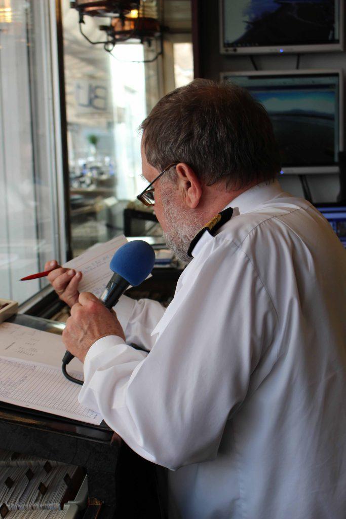 Mann mit Mikrofon in der Hand liest von einer Karteikarte ab.