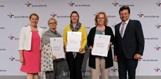 Fünf Personen stehen auf einer Bühne. Drei halten ein Zertifikat in den Händen.