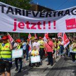 """Bankanstellte in Warnwesten mit Banner auf dem """"Tarifvertrag jetzt!!!"""" steht"""