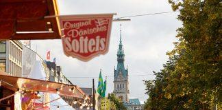 Buden und Menschen entlang der Alster beim Alstervergnügen. Im Hintergrund ist der Turm des Hamburger Rathauses.