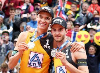 Beachvolleyball-Vizemeister Julius Thole und Clemens Wickler mit ihren Silbermedaillen, im Hintergrund feiernde Fans