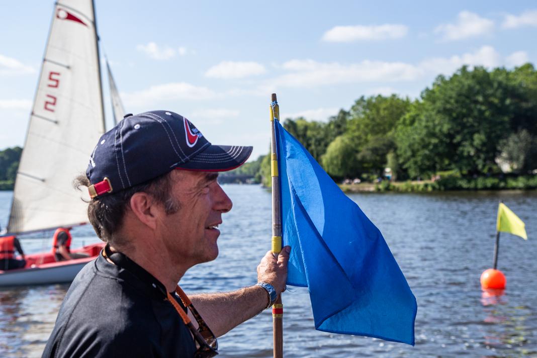 Philipp Hatje wartet mit der blauen Zielflagge im Zieleinlauf.