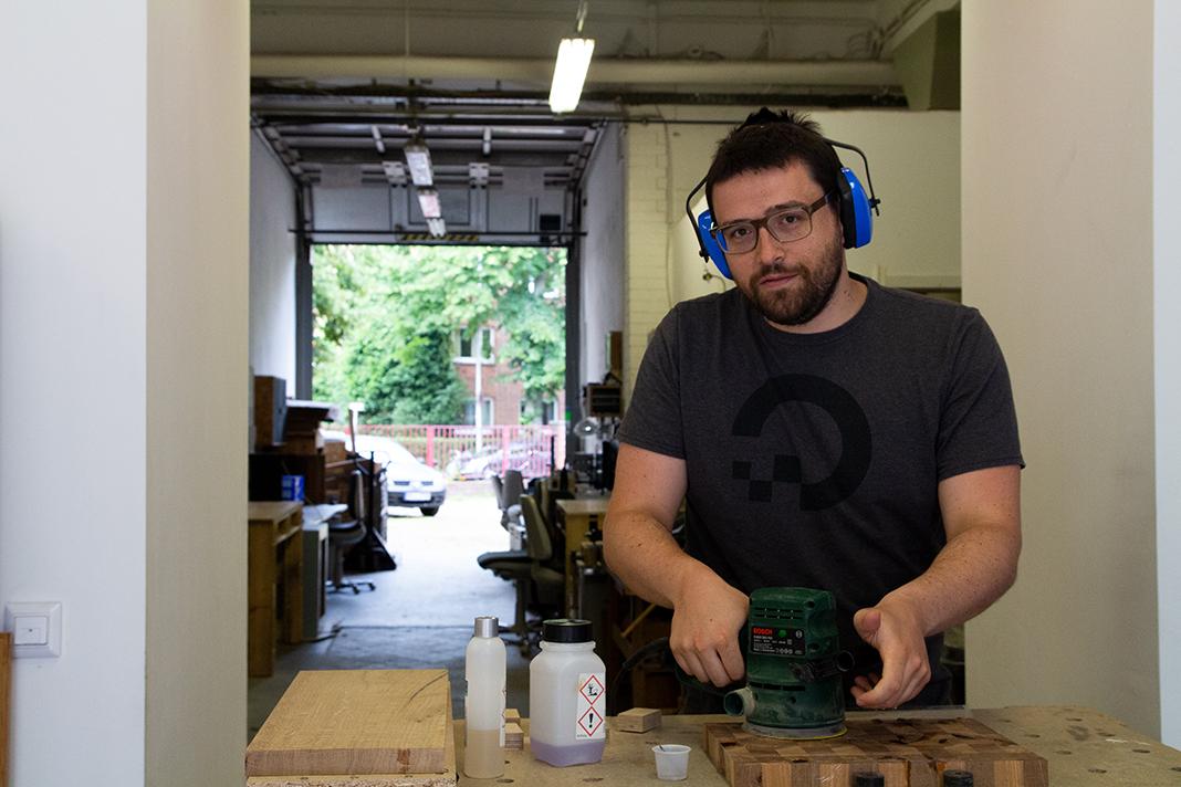 Moritz Stückler steht in seiner Welcome Werkstatt und schleift ein Brettchen ab. Foto: Max Nölke