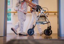 Ältere Frau geht mit einem Rollator und einem Pfleger über den Gang.