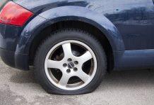 Ein beschädigter Reifen an einem blauen Wagen.