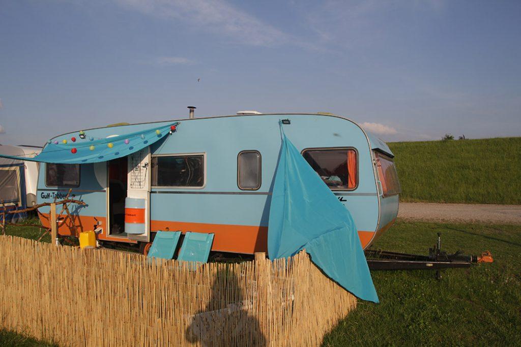 Roberto Passarottos umgebauter Wohnwagen in der Seitenansicht. Im Hintergrund ist der Deich zu sehen.