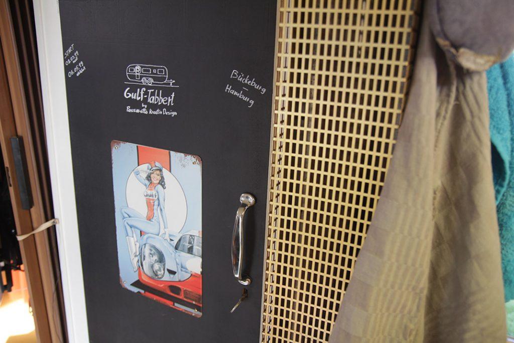 Gulf-Porsche-Schild an einer Innenwand des Wohnwagens