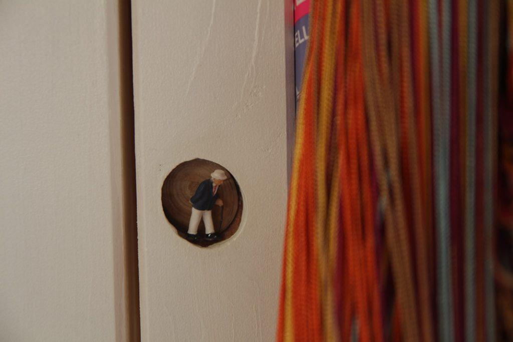 Modellbaufigur in einer kleinen kreisrunden Ausfräsung in der Wand des Wohnwagens