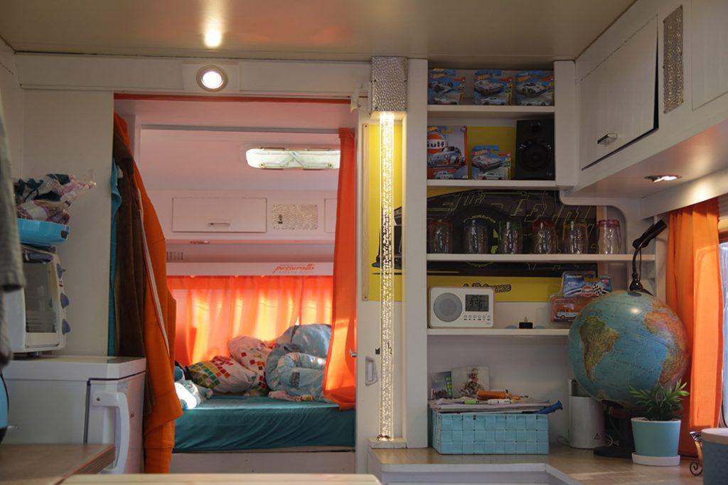Innenansicht des Wohnwagens mit Küche und Bett
