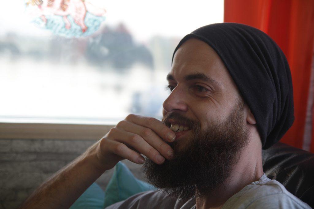 Roberto Passarotto fährt sich durch den Bart und lächelt, Szene in seinem Wohnwagen