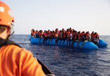 Mittelmeer: Die von der Seenotrettungsorganisation Sea-Eye herausgegebene Aufnahme zeigt einen Seenotretter (l) der zu einem Flüchtlingsboot schaut. Nach dem Drama um das Rettungsschiff «Sea-Watch 3» hat nun eine andere deutsche Hilfsorganisation Migranten vor Libyen mit ihrem Schiff aufgenommen. Die «Alan Kurdi» habe 65 Menschen in internationalen Gewässern auf einem überladenem Schlauchboot vor Libyen entdeckt und gerettet, teilte die Regensburger Organisation Sea-Eye am Freitag mit.