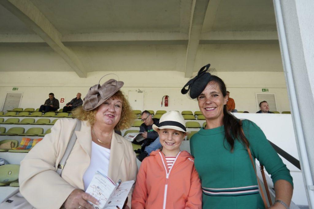 Zwei Damen mit Fascinatoren und ein junges Mädchen in der Mitte mit Strohhut
