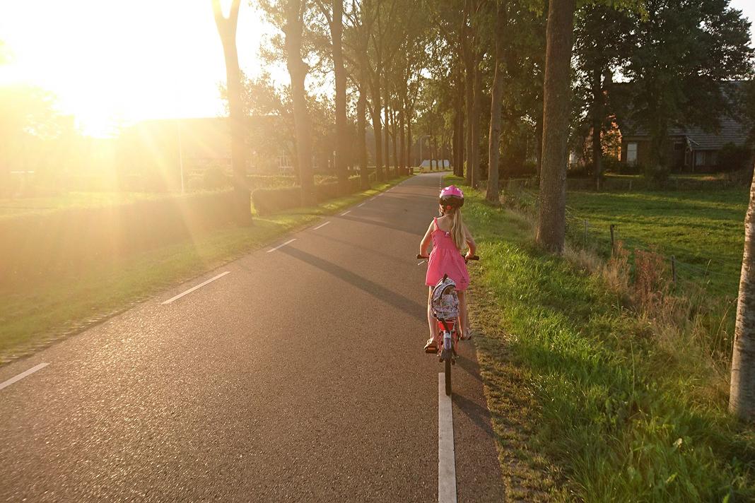 Ein Mädchen fährt auf einer Landstraße, die Sonne geht unter.