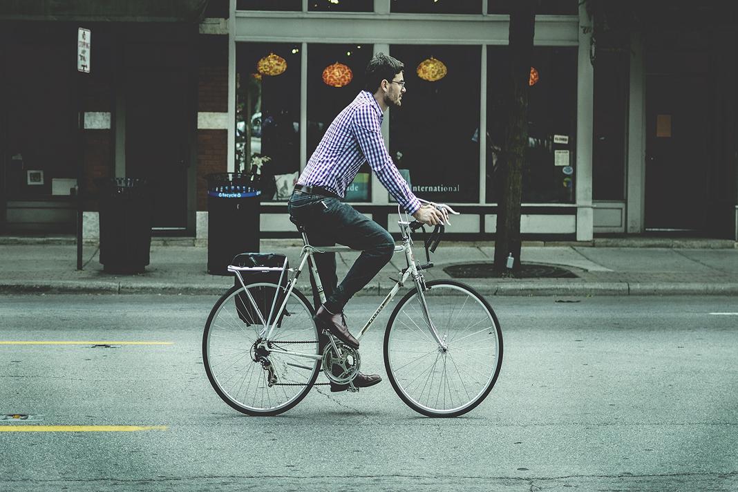 Ein Mann fährt auf der Straße mit einem Fahrrad.