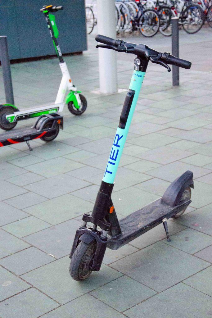 E-Scooter des Anbierters Tier parkt vor einem Fahrradständer. Im Hintergrund zwei weitere Escooter anderer Anbieter.