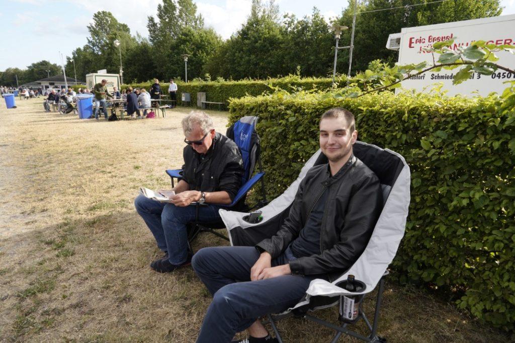 Vater und Sohn sitzen beide in Campingstühlen mitsamt Bier am Rand der Rennbahn und schauen sich das Rennprogramm an