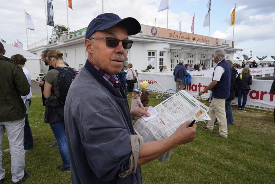 Mann mit Mütze und Sonnenbrille schaut ins Rennprogramm und bereitet seine nächste Wette vor