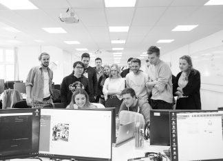Menschen schauen gemeinsam auf einen Bildschirm.