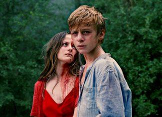 Gloria steht mit starrem Blick und blutverschmiertem Gesicht neben Paul.