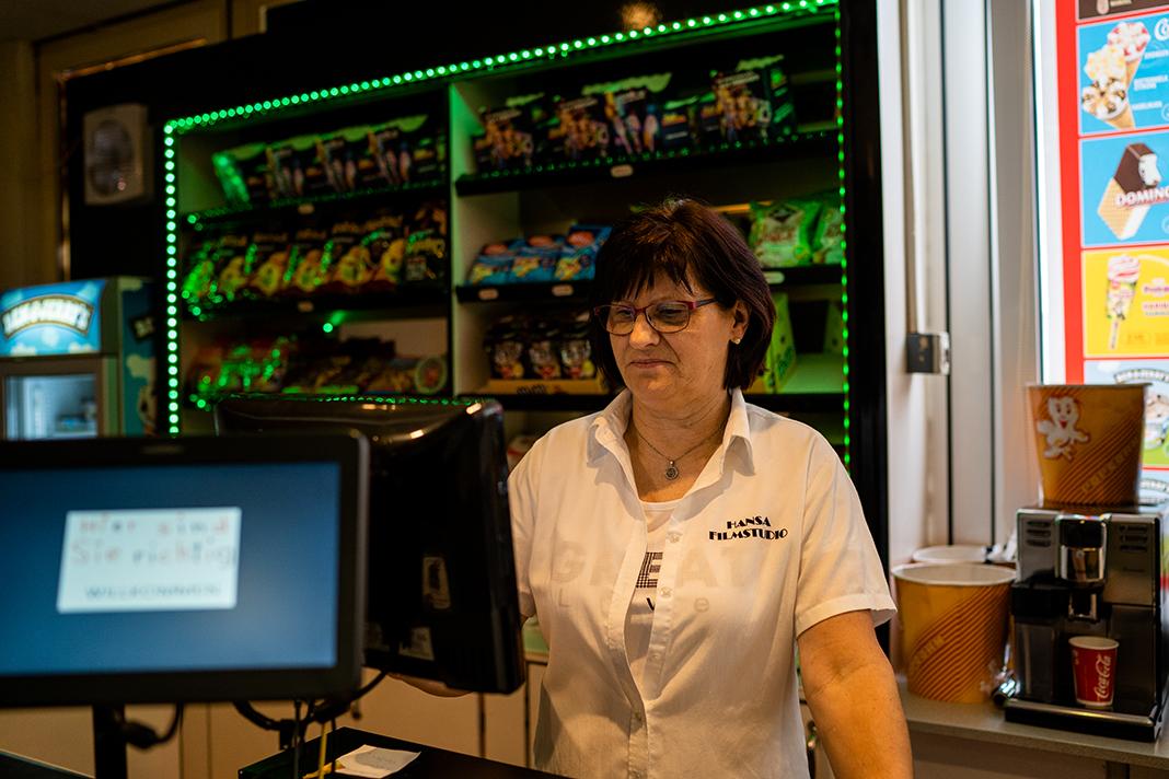 Frau Postrach steht hinter der Kasse der Snack-Bar