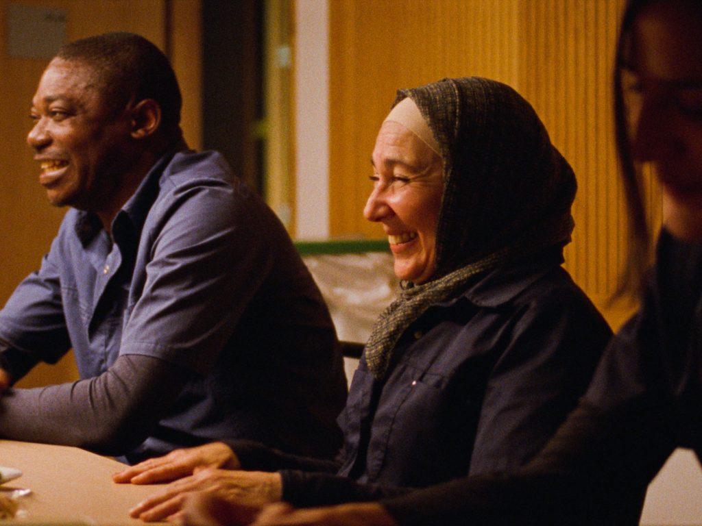Frau und Mann sitzen an einem Tisch und lachen.