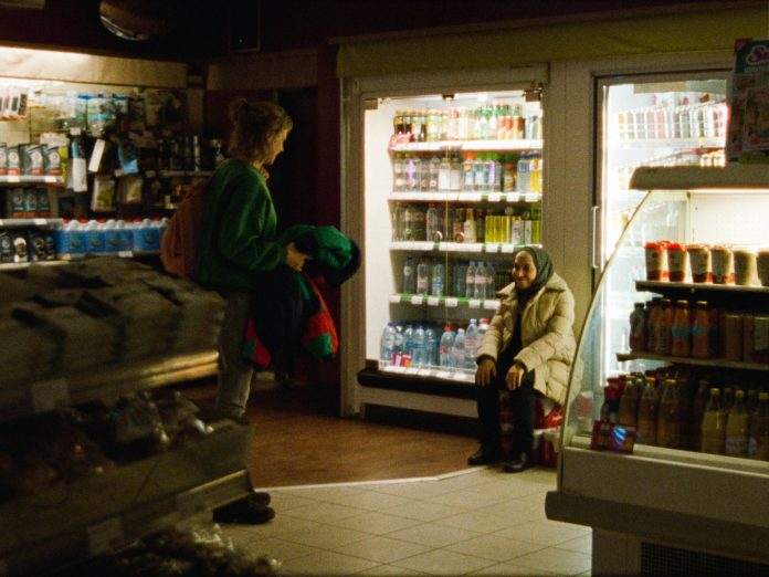 Frau sitzt in einem Supermarkt vor den Kühlschränken.
