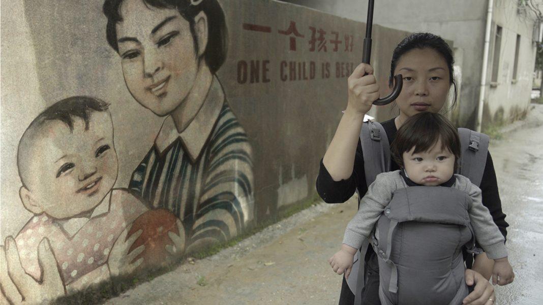 Nanfu Wang mit ihrem Kind vor einer Wand mit chinesischer Ein-Kind-Propaganda: