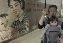 """Nanfu Wang mit ihrem Kind vor einer Wand mit chinesischer Ein-Kind-Propaganda: """"One Child is best"""""""