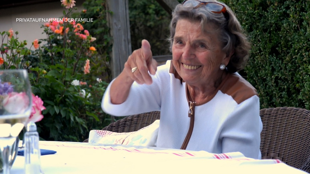 Annemarie Dose sitzt am Tisch im Garten und lacht