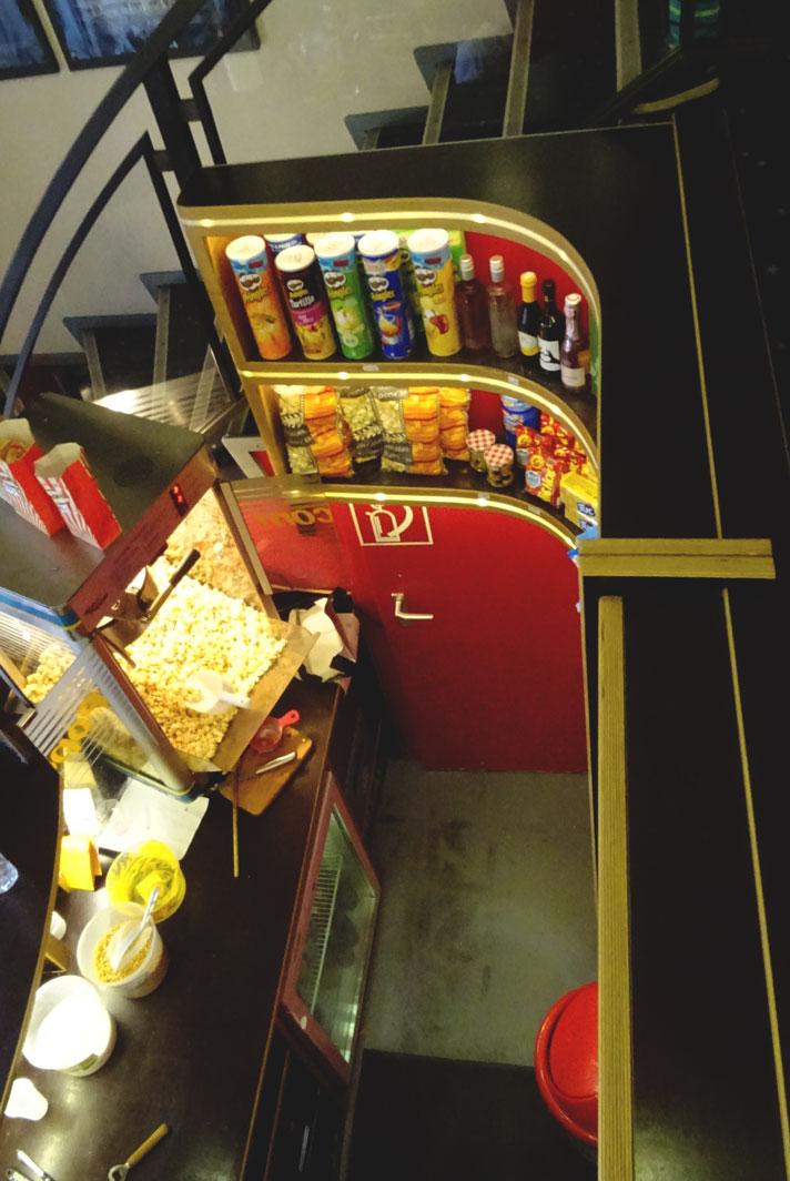 Popcorn, Chips und Getränke stehen in den runden Regalen im Eingangsbereich.
