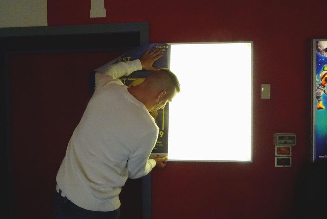 Thorsten Leibner wechselt das Filmplakat im Schaukasten vor Kinosaal 1.