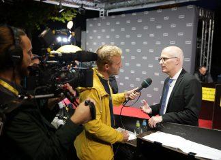 Simon hält für eine Aufnahme Dr. Peter Tschentscher ein Mikrofon hin. Nikolas hält die Kamera.