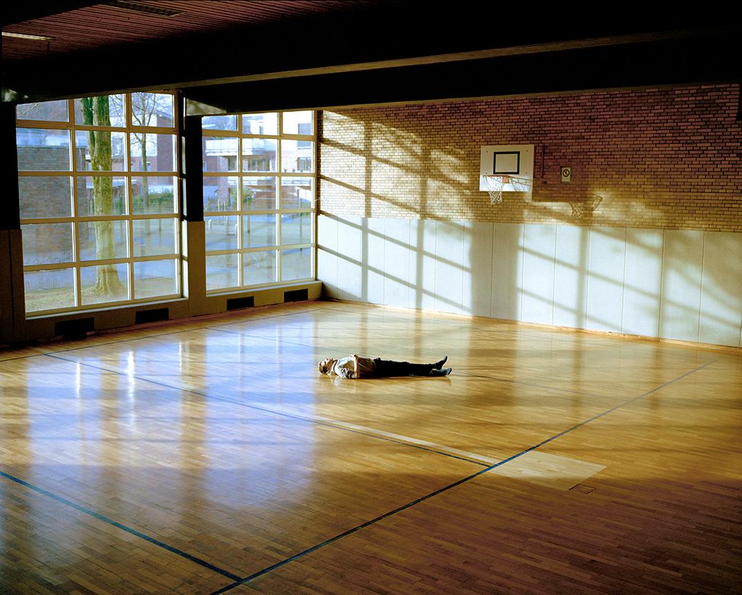 Mann liegt auf einem Turnhallen Boden.