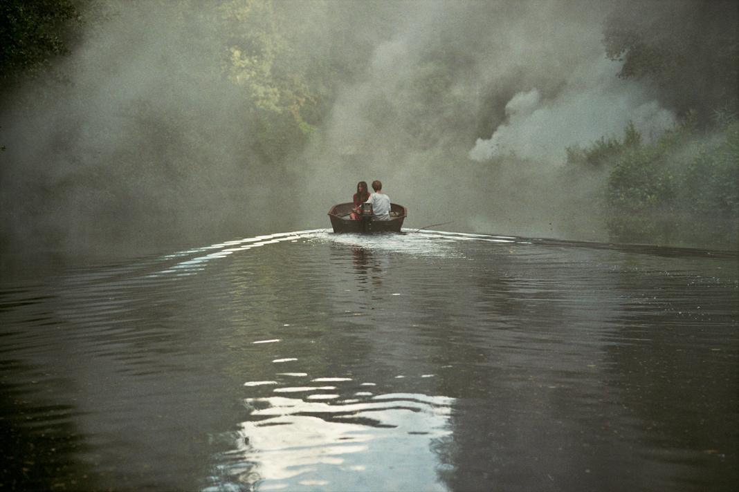 Das Boot fährt auf einem schmalen, vernebelten Fluß, umgeben von dichtem Wald.