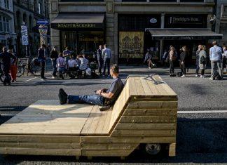 Ein Besucher der Kleinen Johannisstraße hat es sich auf und um den dort stehenden Sitzmöbeln gemütlich gemacht.