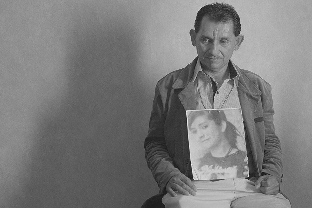 Ein Mann sitzt auf dem Stuhl mit dem Bild seiner vermissten Tochter in der Hand